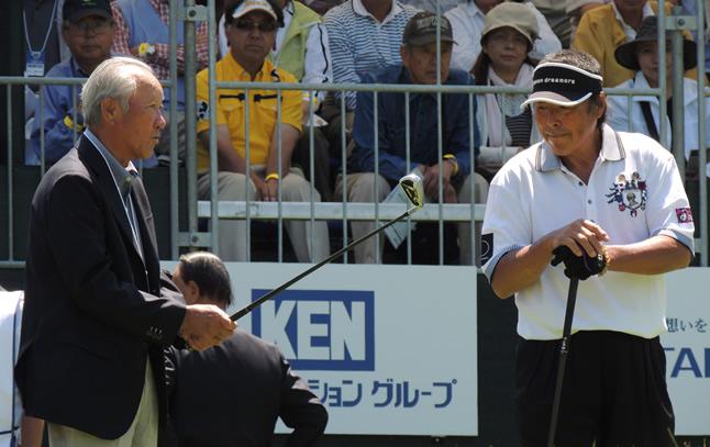 青木功JGTO会長(左)の激励を受けたジャンボ(右)。青木会長はジャンボのアイアンを握ってスタート前のジャンボに話しかけた(6月、日本ゴルフツアー選手権=茨城・宍戸ヒルズ)
